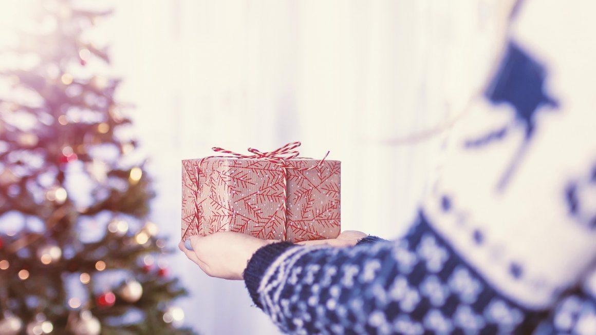 Femme vue de dos qui tient un paquet cadeau dans ses mains et l'approche du sapin de Noël