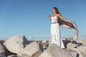 femme sur des rochers portant un robe longue blanche et tenant un foulard