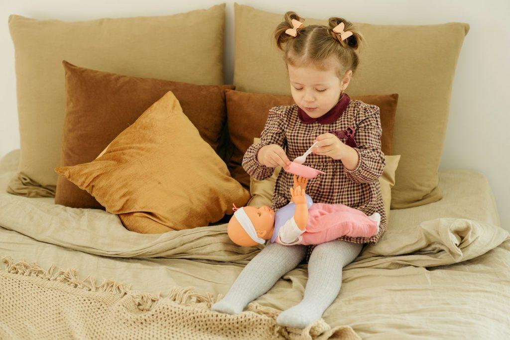 petite fille assise sur un lit qui donne à manger à sa poupée