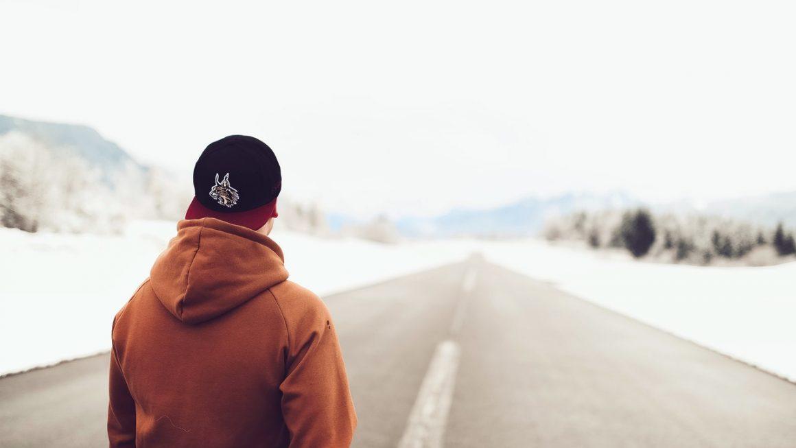 homme de dos sur une route enneigée