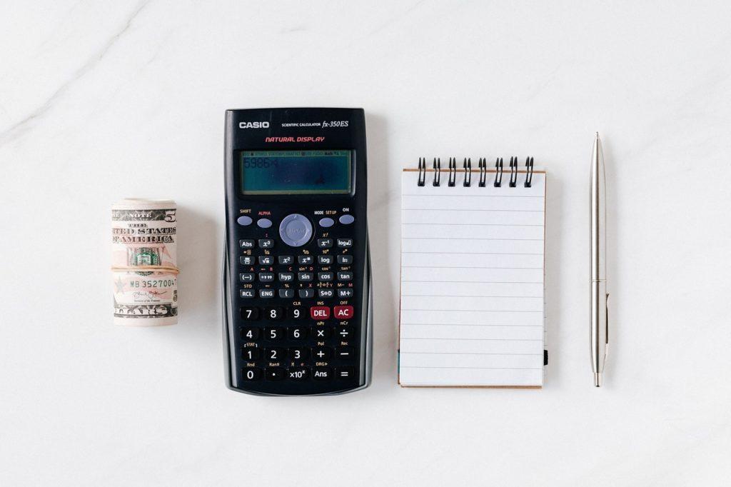 calculatrice posée entre des billets et un carnet