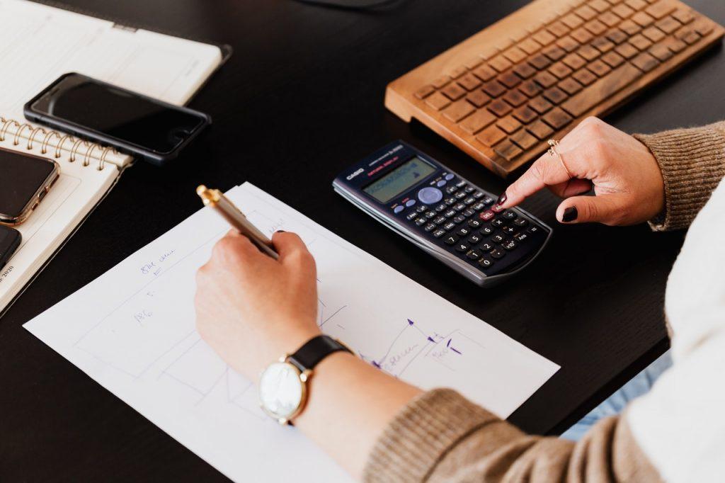 personne qui prend des notes et utilise une calculatrice