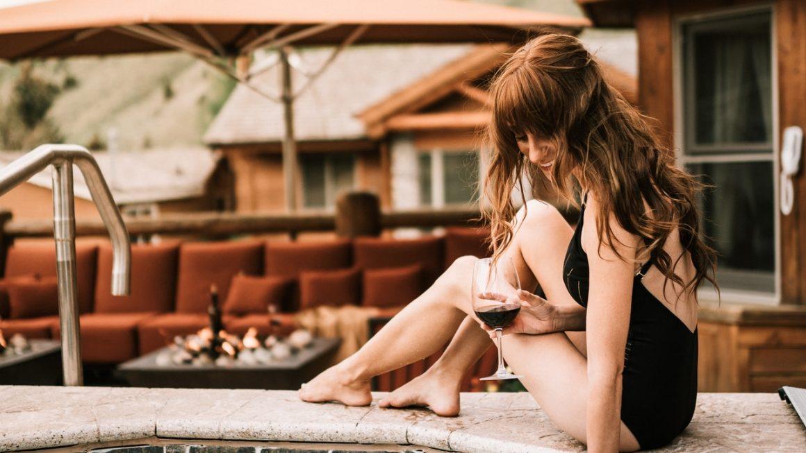 femme en maillot de bain qui vérifie la température de l'eau d'un bassin