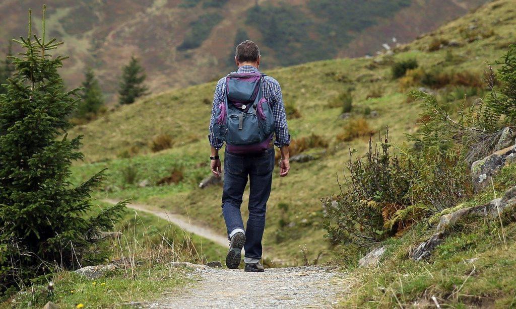 homme qui porte un sac à dos de randonnée