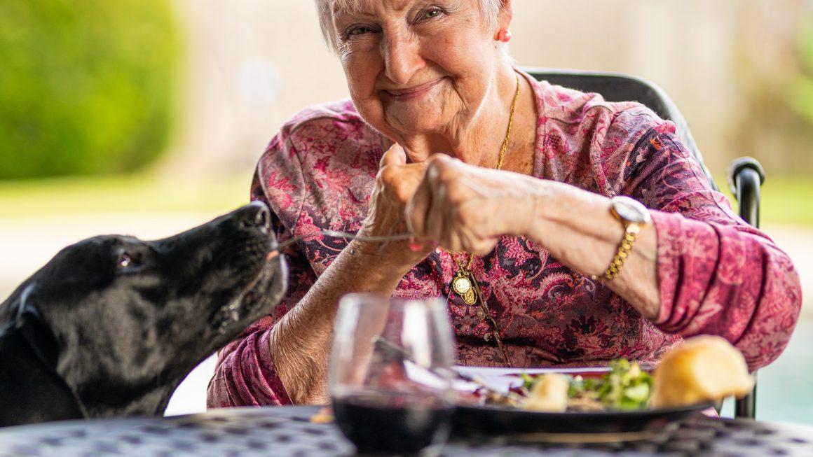 femme âgée mange avec le sourire et en donne au chien